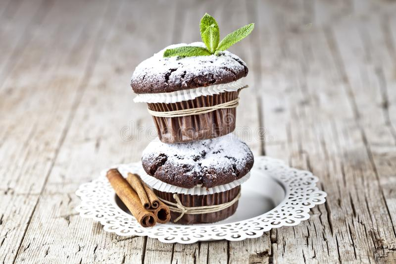 Chocolate dark muffins with sugar powder, cinnamon sticks and mint leaf on white plate on rustic wooden table royalty free stock image