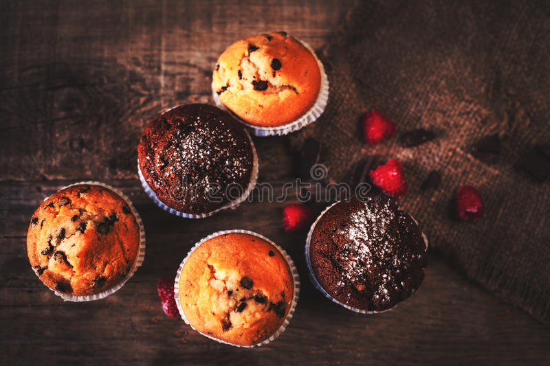Chocolate dark muffins on wooden background with powdered sugar royalty free stock photography