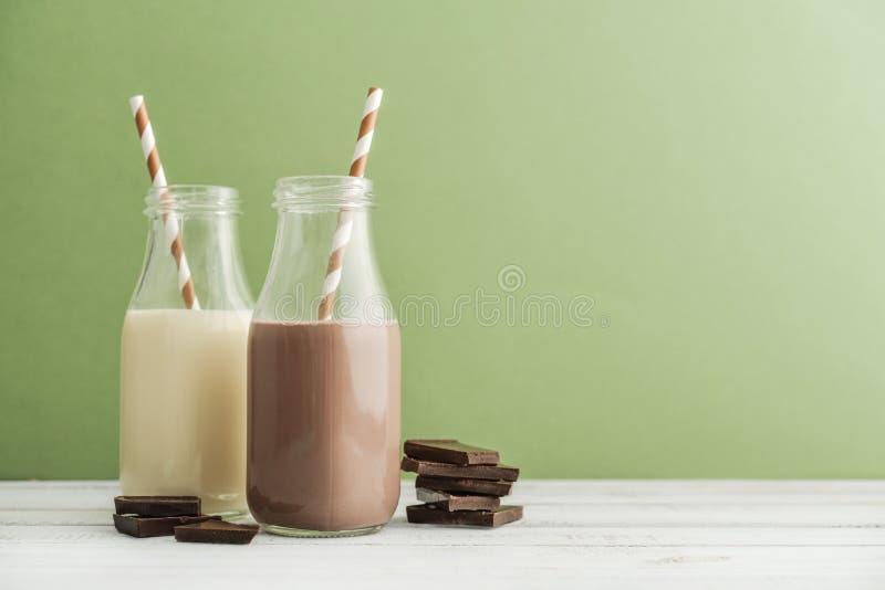 Chocolate de duas garrafas e leite do vanila fotos de stock