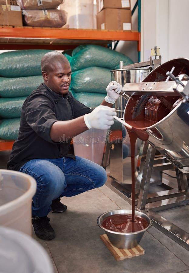 Chocolate de fusión de colada del obrero de la confitería en un cuenco imagen de archivo libre de regalías