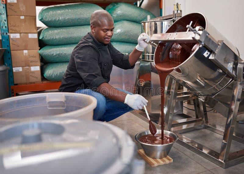 Chocolate de fusión del trabajador mientras que trabaja en una fábrica de la confitería imagenes de archivo