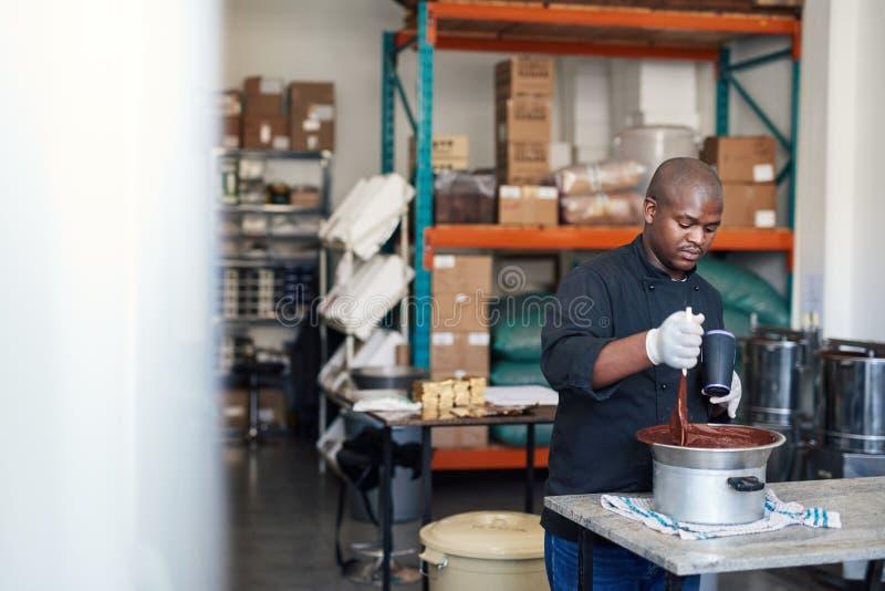 Chocolate de fusión y de mezcla del trabajador en un cuenco fotografía de archivo libre de regalías