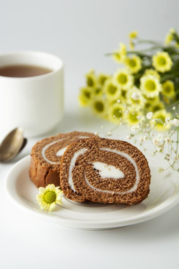 Chocolate de la torta de chocolate del rollo suizo con crema Postre Taza y torta de caf? del desayuno Fondo ligero fotos de archivo libres de regalías