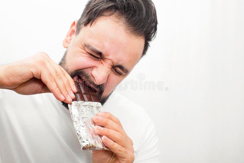 Chocolate de mordedura do homem gordo farpado é duro para ele fazer isso O homem novo guarda a barra com ambas as mãos Isolado no fotografia de stock royalty free