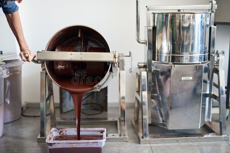Chocolate derretido que es vertido en un envase de la fábrica imagen de archivo libre de regalías