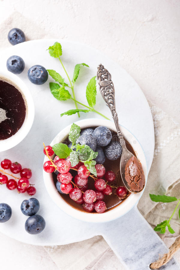 Chocolate dessert with berries. Delicious chocolate dessert with berries and mint served in ramekin. Top view. Copy space royalty free stock photography