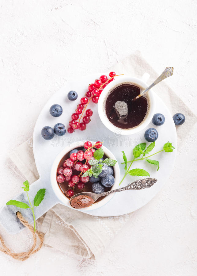 Chocolate dessert with berries. Delicious chocolate dessert with berries and mint served in ramekin. Top view. Copy space stock photography