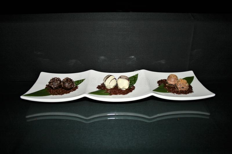 Chocolate dipped Macadamia nuts on a white plate with a black background stock photo