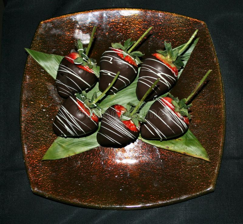 Chocolate dipped strawberries on a glass plate with a black background stock photography