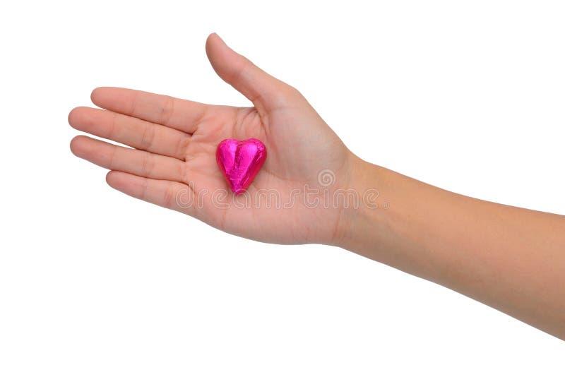 Chocolate do coração na mão da mulher foto de stock royalty free