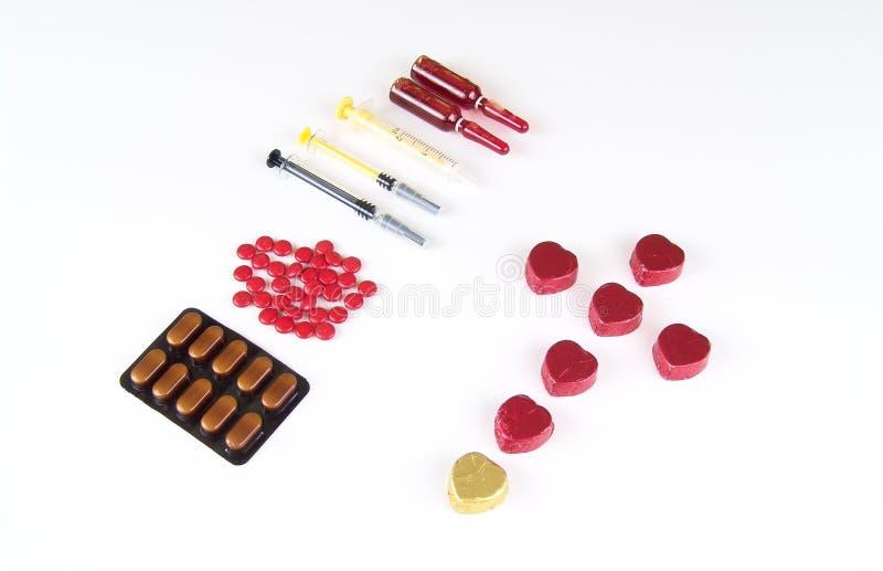 Chocolate doce da forma do coração envolvido na folha e nas medicinas fotografia de stock