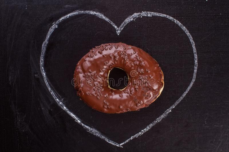 Chocolate donut and drawn heart shape. Hand drawn chalk heart and iced cake on black surface. Happy Valentines Day stock photography
