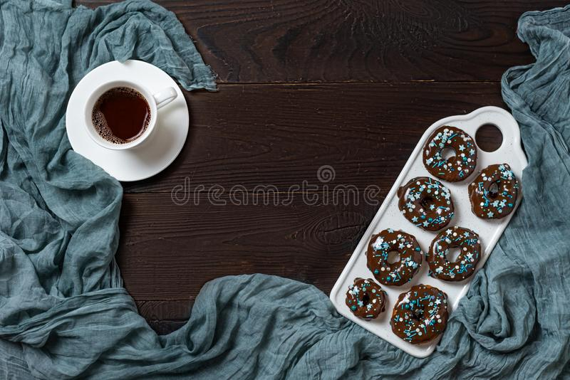 Chocolate donuts and cofee on dark wooden background royalty free stock image