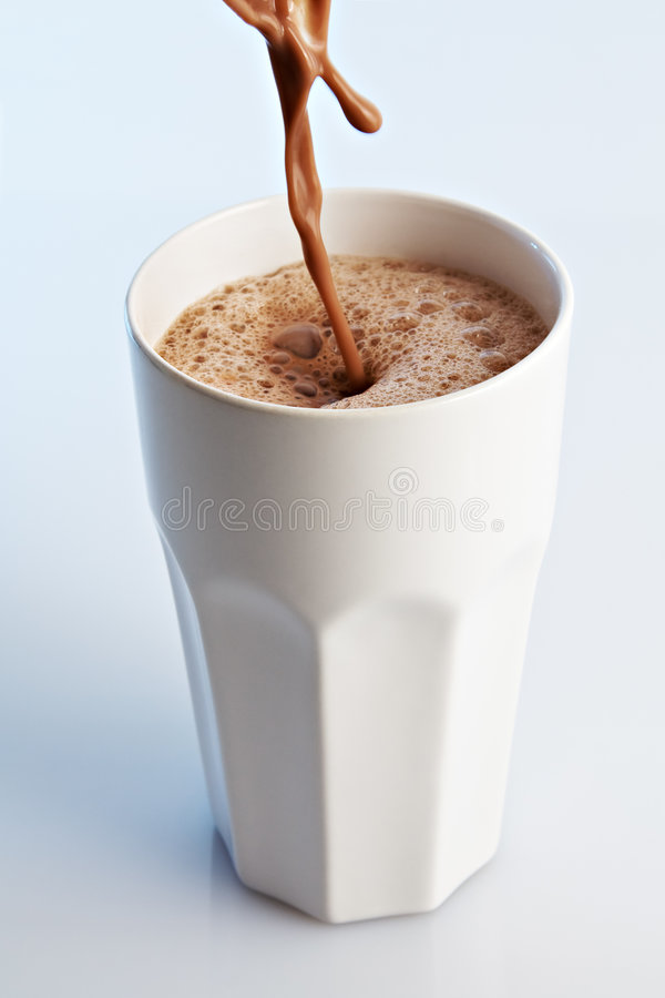 Chocolate Drink. Pouring into a white ceramic glass royalty free stock photo