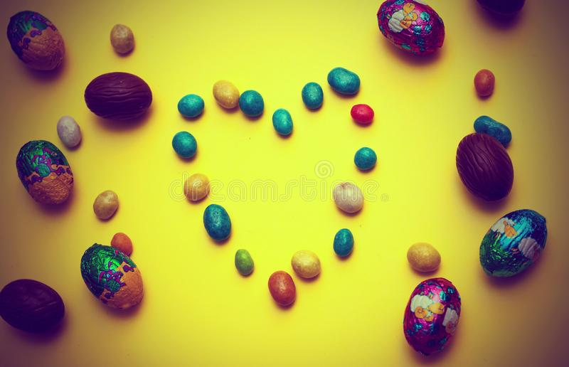Chocolate Easter eggs bows on wooden background. heart of chocolates. chocolate heart royalty free stock image