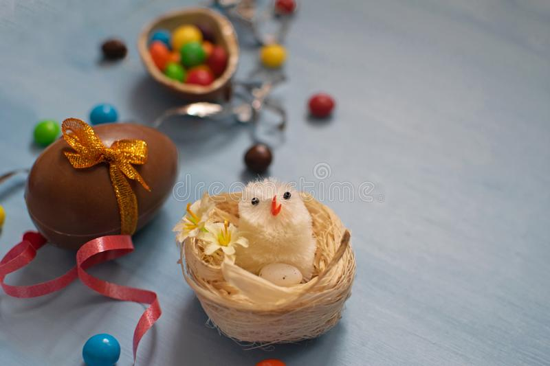 Chocolate Easter eggs and sweets on blue background royalty free stock photography