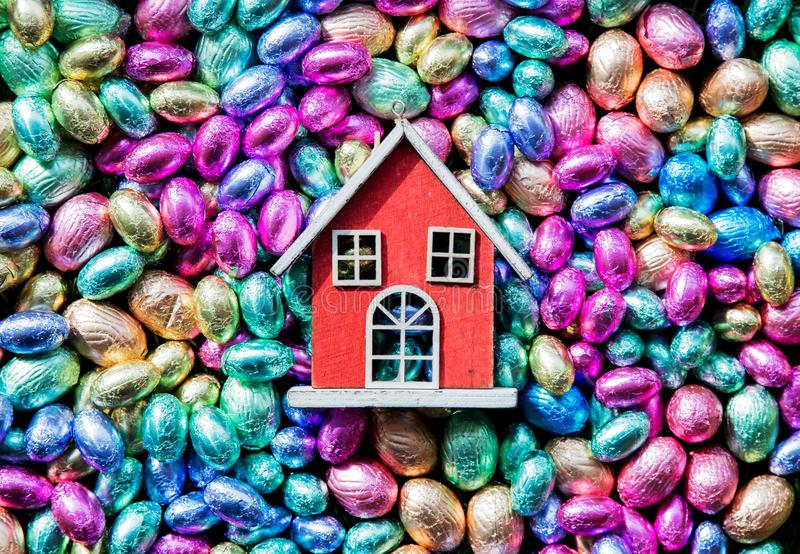 Chocolate Easter eggs and toy house on it stock images