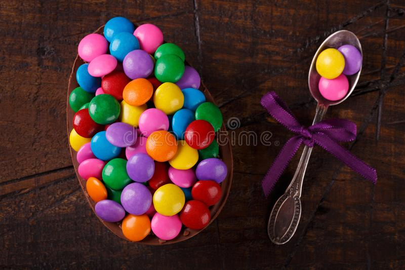 Chocolate egg with filling for Easter on wooden background. Chocolate egg with filling of colorful candy for Easter on wooden background. Selective focus stock images