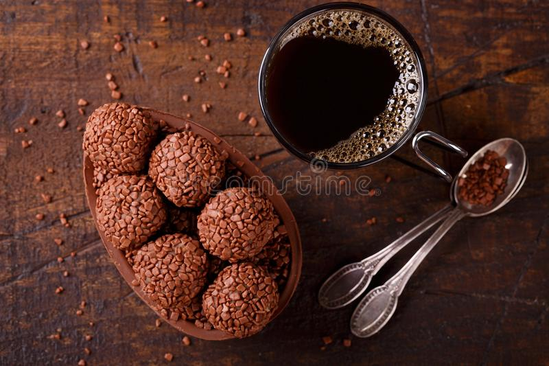 Chocolate egg with filling for Easter on wooden background. Chocolate egg with filling of brigadeiro for Easter and cup of coffee on wooden background. Selective stock photo