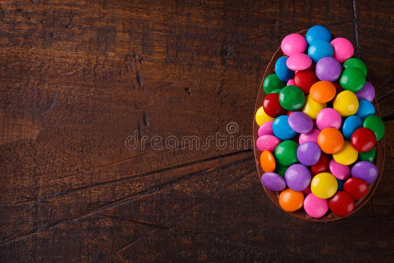 Chocolate egg with filling for Easter on wooden background. Chocolate egg with filling of colorful candy for Easter on wooden background. Selective focus. Copy stock images