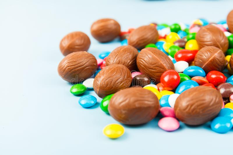 Chocolate eggs and color candy glaze stock photos