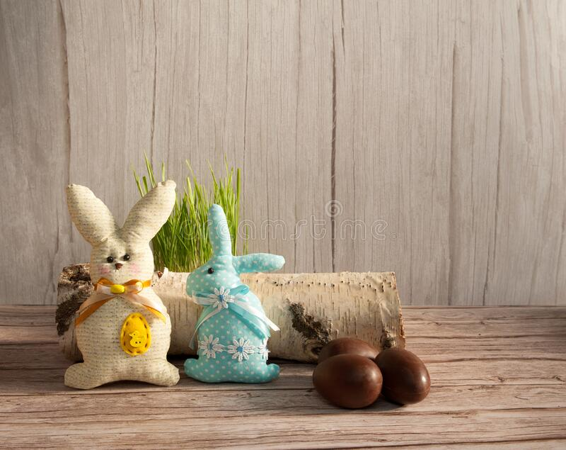 Chocolate eggs, funny handmade textile Easter bunnies and grass on a light wooden background. Easter composition. Chocolate eggs, funny handmade textile Easter royalty free stock image