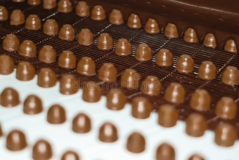 Chocolate fillings in the process of pouring liquid chocolate on the conveyor. Chocolate fillings move on a conveyor to a machine for pouring them with liquid stock photos