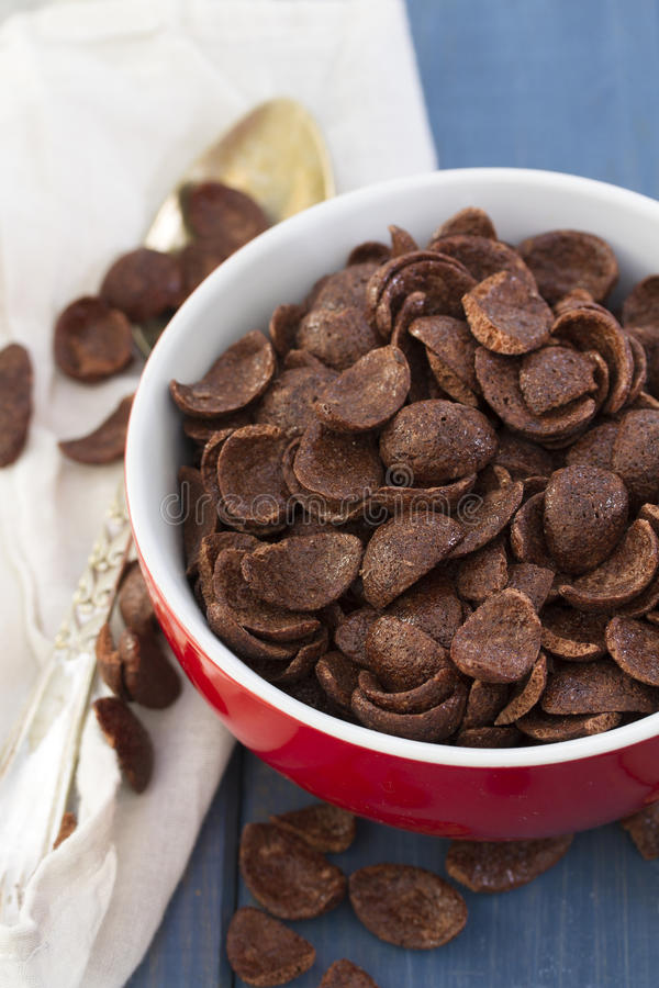 Chocolate flakes in red bowl. On blue background royalty free stock images