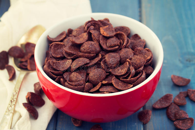 Chocolate flakes in red bowl. On blue wooden background royalty free stock photography