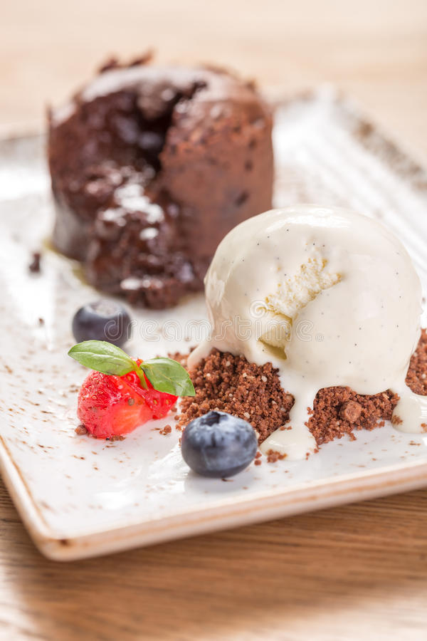 Chocolate fondant lava cake decorated with berries. And vanilla ice cream on the table stock image