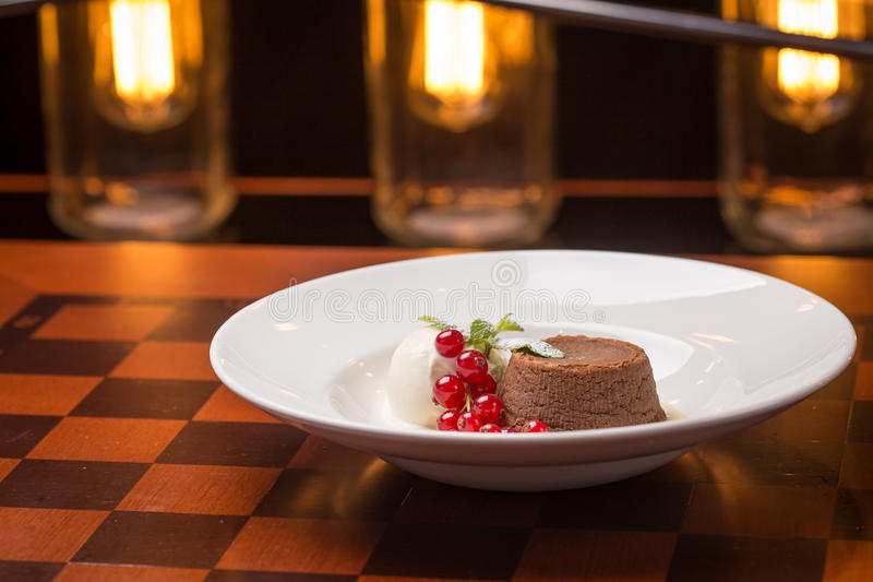 Chocolate fondant lava cake. Decorated with red currant and vanilla ice cream on bright lights background royalty free stock images