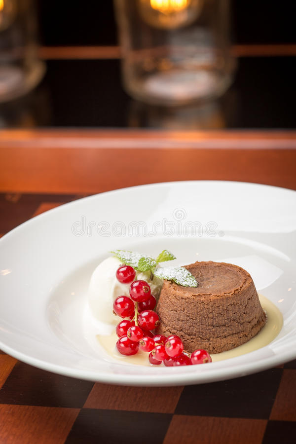 Chocolate fondant lava cake. Decorated with red currant and vanilla ice cream on bright lights background stock photography