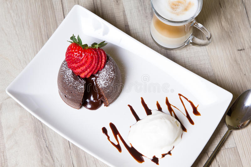 Chocolate fondant lava cake with strawberries and ice cream. Selective focus royalty free stock image