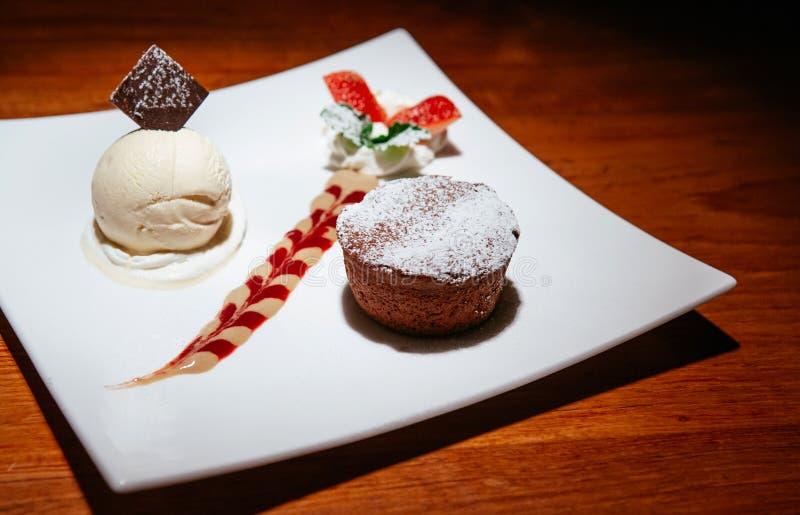 Chocolate fondant lava cake with vanilla ice cream, creamy sauce stock photography