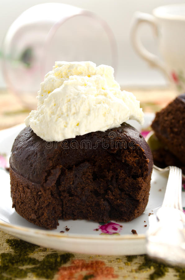Chocolate fondant, souffle cake with whipped cream on decorative plate.  stock images