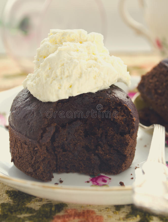 Chocolate fondant, souffle cake with whipped cream on decorative plate. Toned stock photography