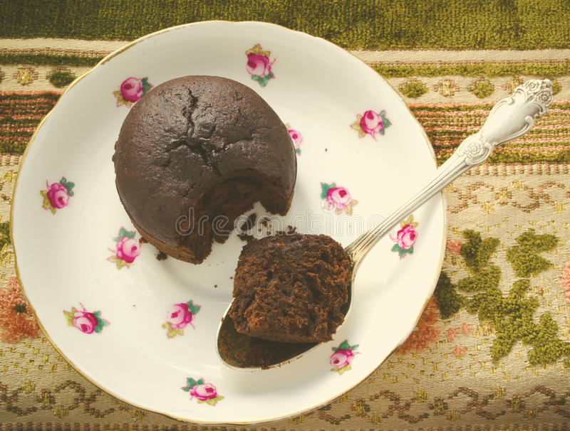 Chocolate fondant, souffle cake with whipped cream on decorative plate. Top view, toned stock image