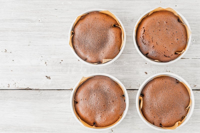 Chocolate fondant on the white wooden table top view. Chocolate fondant in the ramekin on the white wooden table top view royalty free stock images