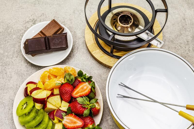 Chocolate fondue. Assorted fresh fruits, two types of chocolate. Ingredients for cooking a sweet romantic dessert. Stone concrete royalty free stock photos