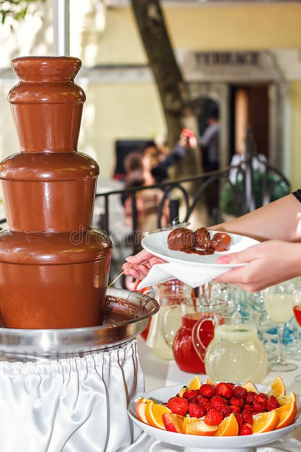 Chocolate fondue with fruits assortment. Female hand dipping strawberry on a skewer into the warm chocolate fondue fountain at the stock image