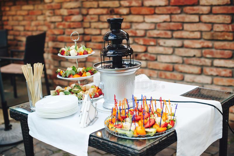 Chocolate fountain. Dessert table with fruits. Fountain on birthday party, event or wedding. Party catering. Sweet table on kids p stock images