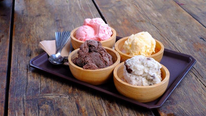 Chocolate gelado, baunilha e morango em copo de vidro em mãos sobre mesa de madeira no café da rua Conceito de sobremesa de alime foto de stock