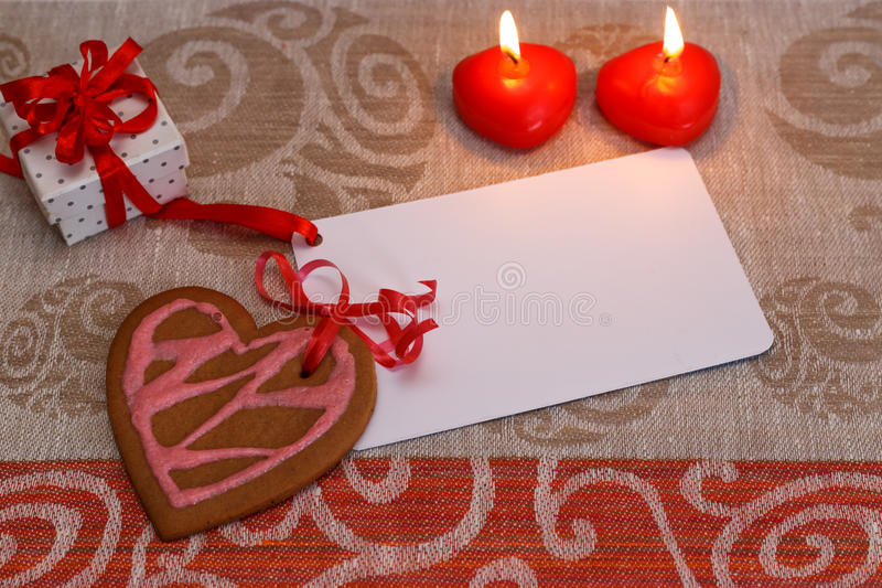 Chocolate gingerbread cookies heart shaped with red and pink icing and red ribbon next on colorful fabric stock photo