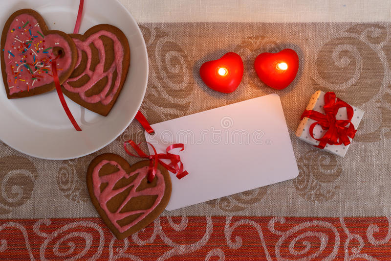 Chocolate gingerbread cookies heart shaped with red and pink icing and red ribbon next on colorful fabric royalty free stock photos