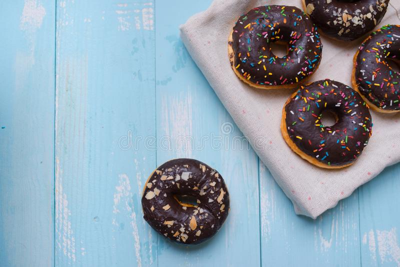 Chocolate glazed donuts on wooden background with blank space stock image
