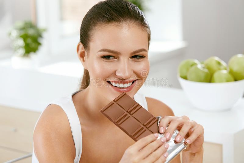 Chocolate. Happy Woman Biting Chocolate Bar. Portrait Of Beautiful Young Smiling Woman Enjoying Dark Chocolate Indoors. Diet And Nutrition Concept. High stock images
