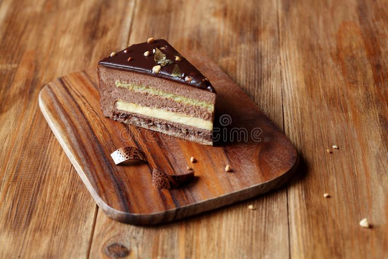 Chocolate Hazelnut Mousse Cake. Piece of layered Chocolate Hazelnut Mousse Cake covered with chocolate glaze and decorated with chocolate elements, on wooden royalty free stock photography