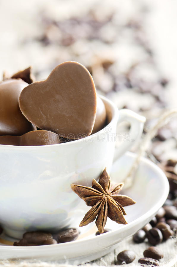 Chocolate heart and coffee beans in white cup. stock photography