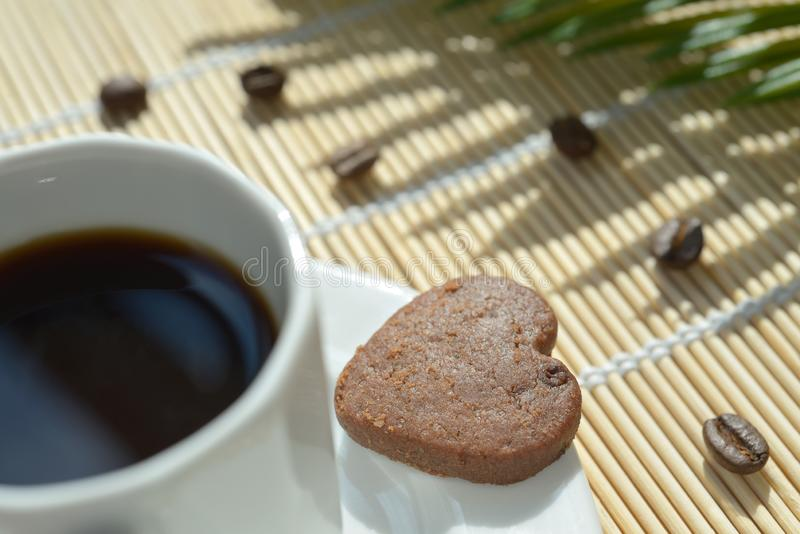 Chocolate heart cookie on saucer Expresso coffee beans. A chocolate heart-shaped cookies on the saucer of a cup filled with expresso coffee. A bamboo table set stock photo