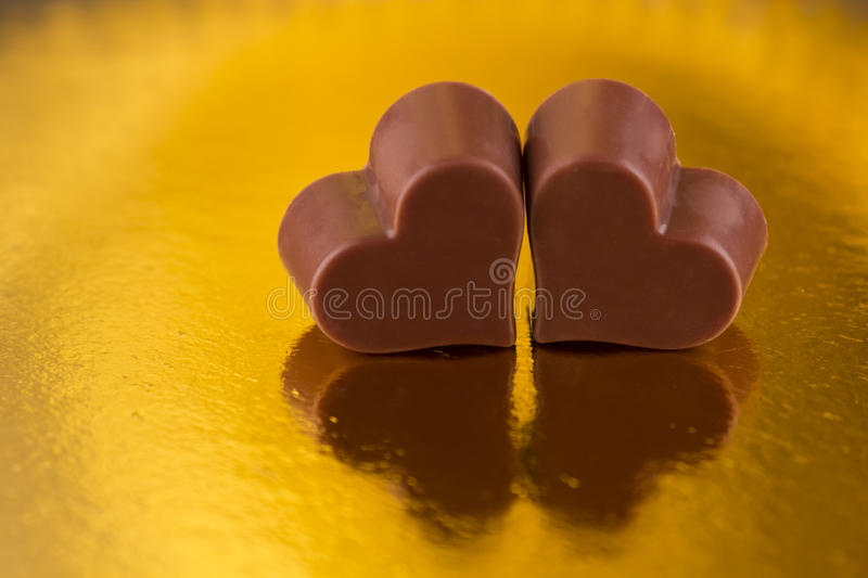 Chocolate hearts on a golden background
